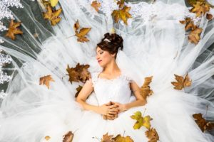 woman lying down in wedding dress surrounded by autumn leaves
